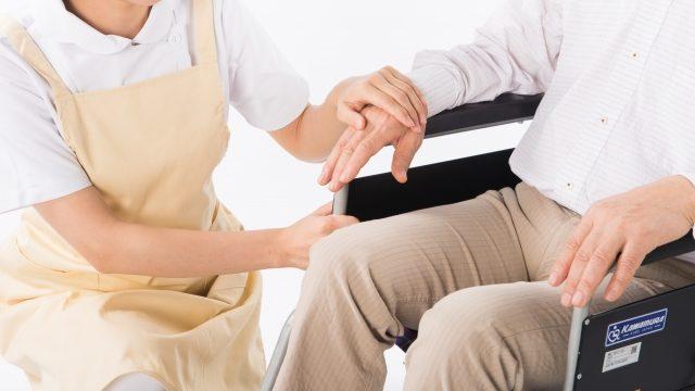 車いすの男性を介護している介護施設の女性