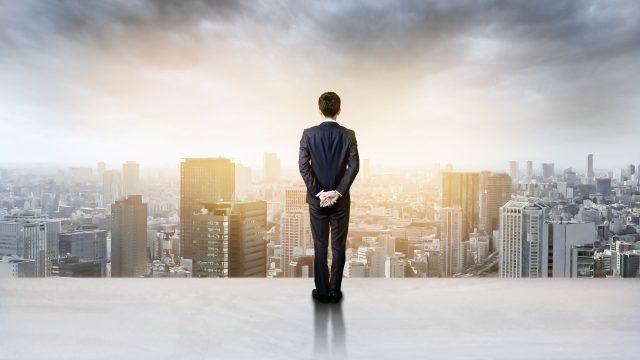 屋上から立ち並ぶ会社を見つめるスーツの男性