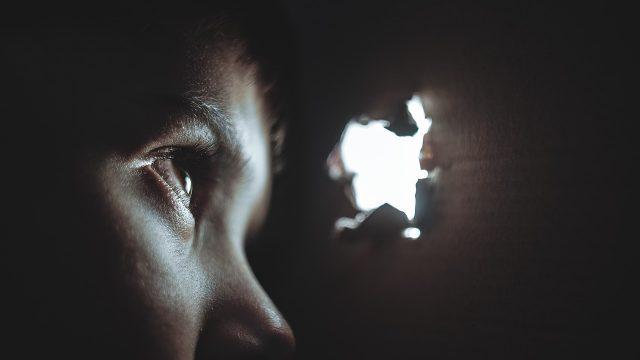 のぞき穴から光を覗く少年