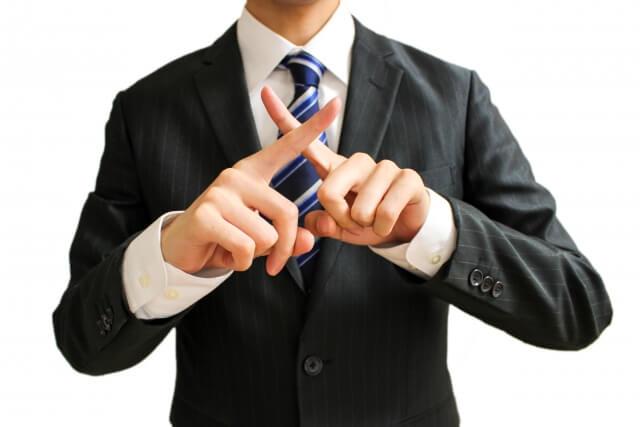 バツ印を手で作るビジネスマン