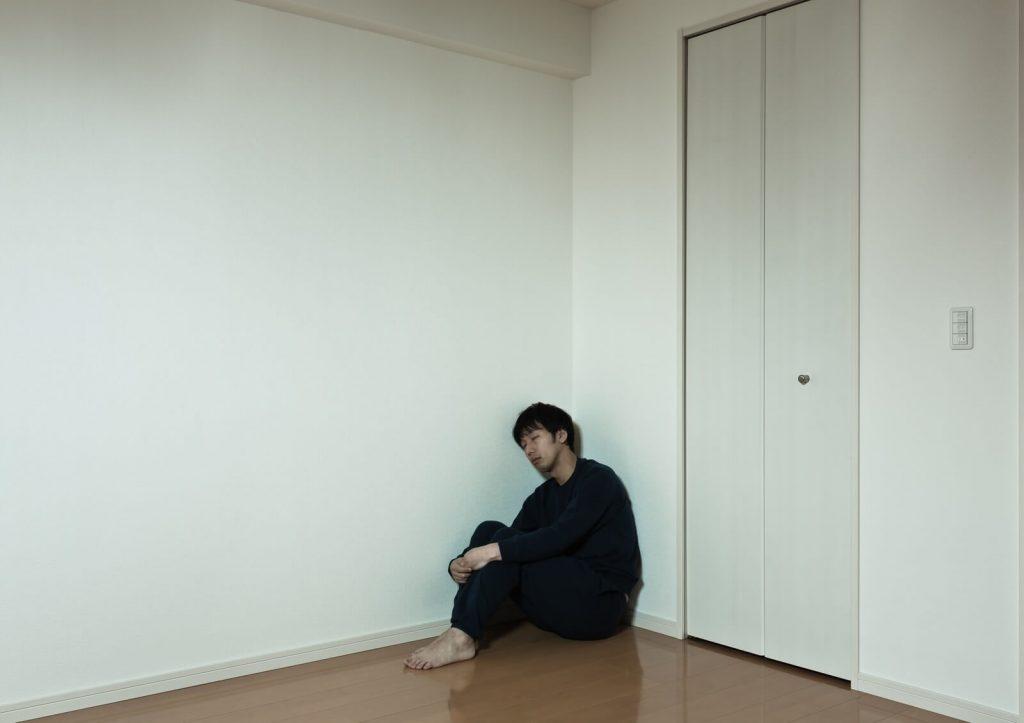 部屋の隅で落ち込む男性