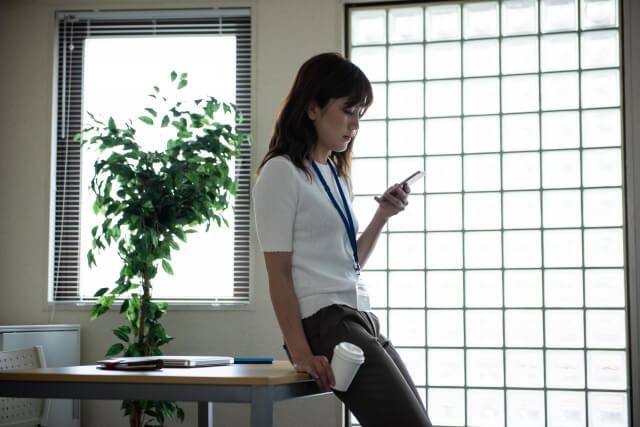 会社で一人でスマホをいじる女性