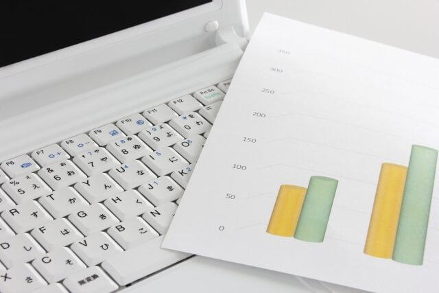 パソコンとグラフが書かれてる資料