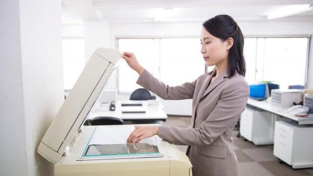 コピー機で作業をするビジネスウーマン