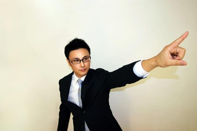 指を指すスーツ姿の男性