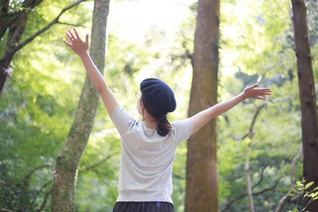 森林で手を広げる女性